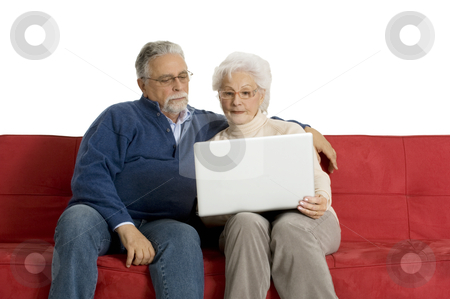Elderly couple on the sofa using a laptop stock photo, elderly couple on the sofa using a laptop by ambrophoto