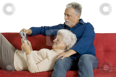 Elderly couple on the couch reading a magazine stock photo, elderly couple on the couch reading a magazine by ambrophoto