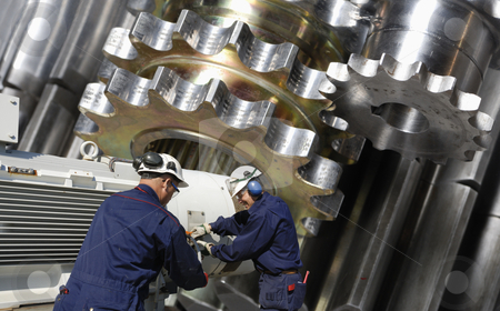 Titanium, gears and worker stock photo, two machinists working with machinery, large gears in background by lagereek