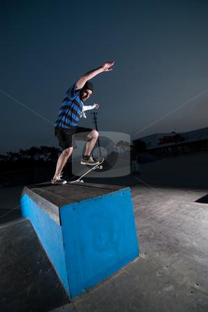 Skateboarder on a slide stock photo, Skateboarder on a slide at night at the local skatepark. by Homydesign
