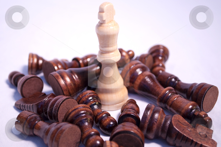 King Chess Piece Standing stock photo, King chess piece standing among fallen opposition chess pieces by Michael T
