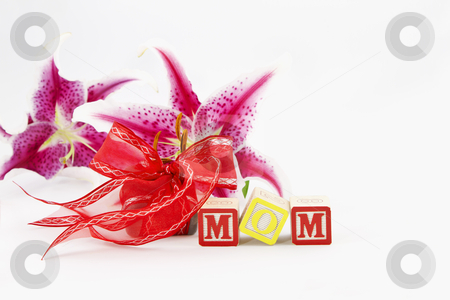 Mom, So Special stock photo, Alphabet blocks spelling out MOM are in front of a red ribbon wrapped gift and two, single lily blooms, all placed on a white background.   by Florence McGinn