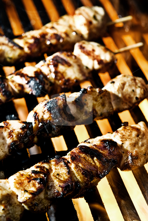 Flame Grilled stock photo, Meat on skewers being flame grilled on a BBQ. by thisboy