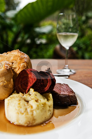 Roast Beef stock photo, A roast beef with mash potato, yorkshire pudding, beetroot chips, gravy and a glass of white wine. by thisboy
