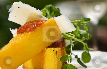 Polenta stock photo, A serving of polenta with a tomato sauce, cheese and watercress, served with a glass of white wine. by thisboy