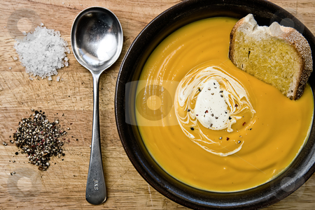 Pumpkin Soup stock photo, Pumpkin soup in a bowl with toast and cream with a spoon and salt and pepper on the side. by thisboy