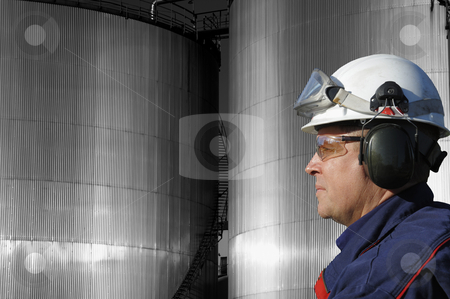 Oil-worker and industrial fuel towers stock photo, engineer, oil-worker, in close-up profile, with large fuel storage towers in background by lagereek