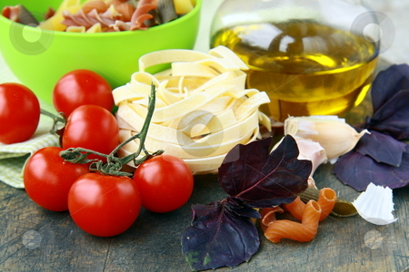 Italian Pasta with tomatoes, olive oil and basil on wooden background stock photo, Italian Pasta with tomatoes, olive oil and basil on wooden background by Olga Kriger