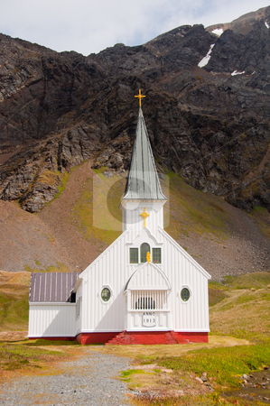 Historic Norwegian Church at Grytviken, South Georgia Island, sub-Antarctica. stock photo, A small, white, steepled church with icy mountains in the background. by liverbird