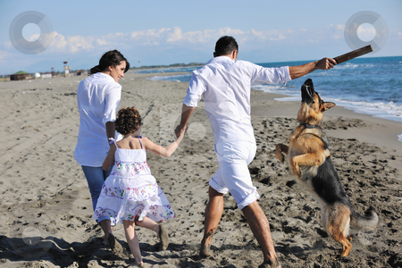 Happy family playing with dog on beach stock photo, happy young family in white clothing have fun and play with beautiful dog at vacations on beautiful beach  by Benis Arapovic