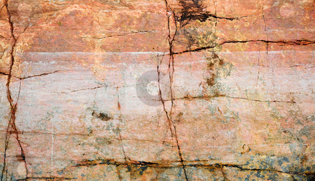 Cracked surface of a rock stock photo, The cracked surface of dirty rock on seacoast by Alexey Romanov