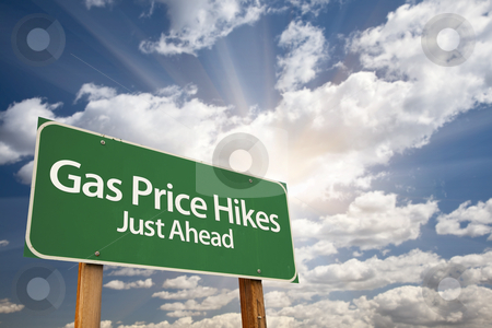 Gas Price Hikes Green Road Sign and Clouds stock photo, Gas Price Hikes Green Road Sign with Dramatic Clouds, Sun Rays and Sky. by Andy Dean