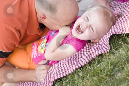 Loving Dad Tickles Daughter in Park stock photo, Loving Dad Tickles His Daughter in the Park. by Andy Dean