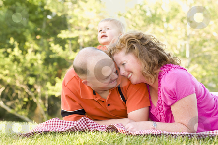 Affectionate Couple with Son in Park stock photo, Affectionate Couple with Adorable Son in the Park. by Andy Dean