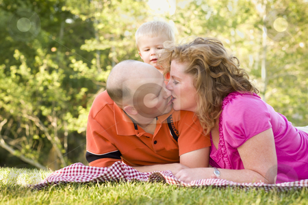 Affectionate Couple Kiss as Cute Son Looks On stock photo, Affectionate Couple Kiss as Adorable Son Watches in the Park. by Andy Dean