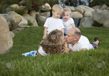 Affectionate Couple Kiss as Cute Twins Look On stock photo, Affectionate Couple Kiss as Adorable Twins Watch in the Park. by Andy Dean