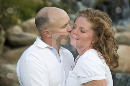 Attractive Couple Pose for Portrait in the Park. stock photo, Happy, Attractive, Affectionate Couple Kiss on Cheek in the Park. by Andy Dean