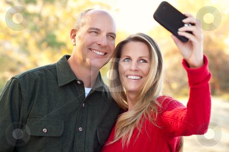 Attractive Couple Pose for a Self Portrait Outdoors stock photo, Happy, Attractive Couple Pose for a Self Portrait Outdoors. by Andy Dean