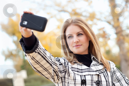 Pretty Young Woman Taking Picture with Camera Phone stock photo, Pretty Young Woman Taking Picture with Camera Phone in the Park One Fall Day. by Andy Dean