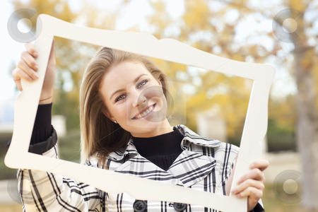 Pretty Young Woman Smiling in the Park with Picture Frame stock photo, Pretty Young Woman Smiling in the Park on a Fall Day with Picture Frame. by Andy Dean