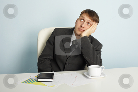 Businessman pensively looks upwards stock photo, The businessman pensively looks upwards sitting at a table by Alexey Romanov