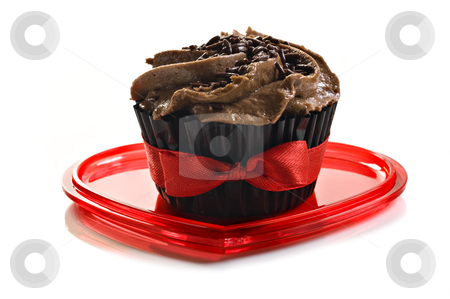 Chocolate cupcake with red bow on a heart shaped plate stock photo, Chocolate cupcake with red bow on a heart shaped plate by tish1
