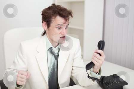 Person emotionally communicates with phone at office stock photo, The person emotionally communicates with phone at office by Alexey Romanov