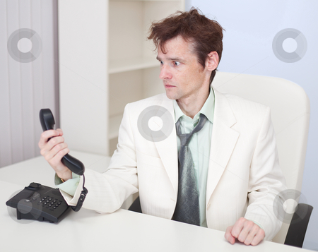 Young man has finished conversation with chief at office stock photo, The young man has finished conversation with the chief sitting at a table at office by Alexey Romanov