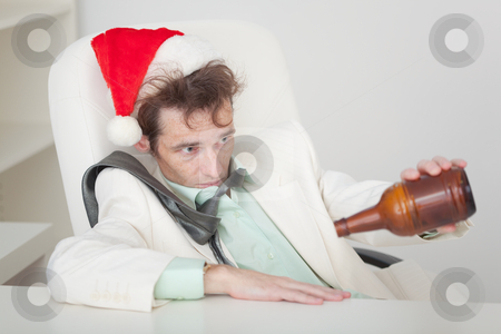 Drunken person in Christmas cap with bottle in a hand stock photo, The drunken person in a Christmas cap with a bottle in a hand by Alexey Romanov