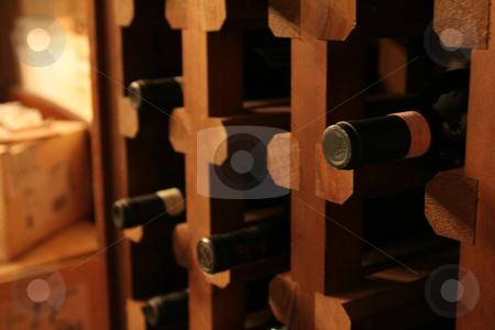 Wine Bottle Rack stock photo, A bunch of wine bottles in a rack in a wine cellar.  by Chris Hill