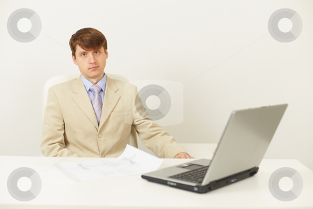 Serious man in light jacket sits at a table stock photo, The serious man in a light jacket sits at a table (studio shot) by Alexey Romanov