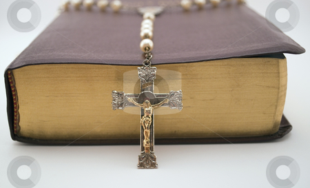 Rosary on Holy Bible stock photo, Low angle shot of rosary leaning over the side of a closed bible by Michael T