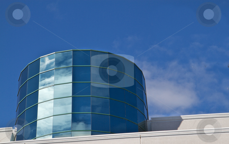 Angled Cylinder Building stock photo, Angled reflective windowed Cylinder Building reflecting blue sky and clouds by bobkeenan