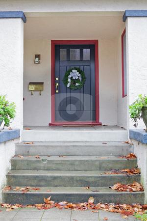 Black door Stucco Home stock photo, Maroon bordered black door of beige stucco house with Christmas wreath by bobkeenan