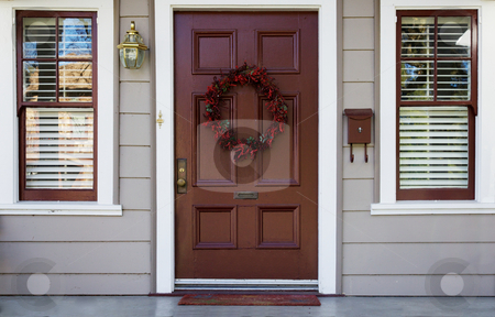 Burgundy door and 2 windows stock photo, Home burgundy door with wreath with two white trimmed blinded windows by bobkeenan