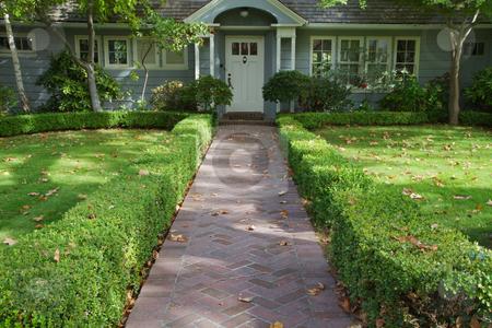 Green bush lined home entrance stock photo, Green bush lined home brick entrance to a white doored gray home by bobkeenan
