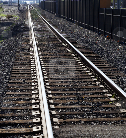 Light Rail Tracks stock photo, City light rail tracks disappearing into distance with black metal fence by bobkeenan