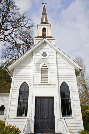 Small old Chruch stock photo, Small old Church with two windows and black door with trees and sky background by bobkeenan
