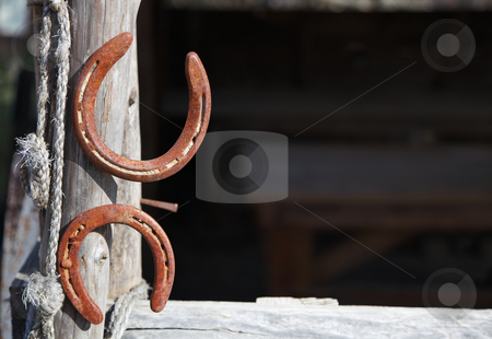 Two horshoes stock photo, Two red rusted horseshoes with dark soft focus barn in background by bobkeenan