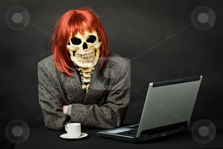 Man dressed as death sits at table with computer stock photo, A man dressed as death sits at a table with a computer by Alexey Romanov