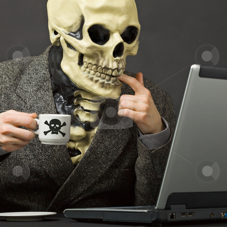 Skeleton drinks poisonous coffee at table with laptop stock photo, The skeleton drinks poisonous coffee sitting at a table with the laptop by Alexey Romanov