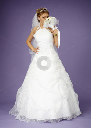 Bride in white dress with bouquet stock photo, Young bride in a white dress with a bouquet on purple background by Alexey Romanov