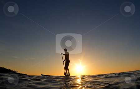 Silhouette of a man paddling his surf board at sunset stock photo, A young man paddles his surfboard in to shore at sunset by mojojojo