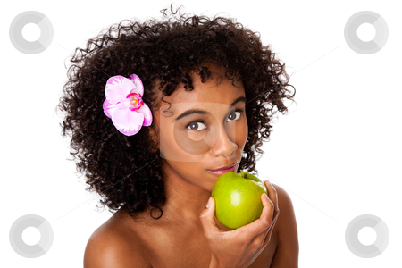 Healthy woman eating apple stock photo, Beautiful happy woman with orchid flower in curly hair eating healthy green apple, isolated. by Paul Hakimata
