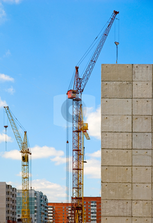Building crane stock photo, Building crane and building under construction against blue cloudy sky   by olinchuk