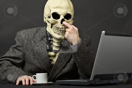 The skeleton picks in a nose stock photo, The skeleton picks in a nose on table with laptop by Alexey Romanov