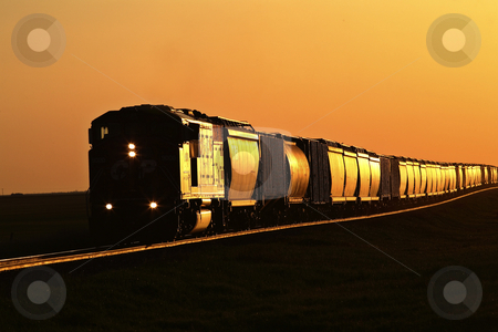 Setting sun reflecting off train and track stock photo, Setting sun reflecting off train and track by Mark Duffy