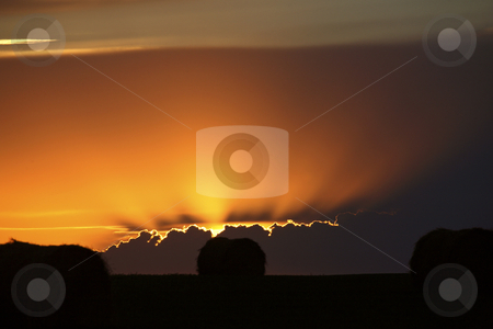 Setting sun peaking out from storm clouds in Saskatchewan stock photo, Setting sun peaking out from storm clouds in Saskatchewan by Mark Duffy