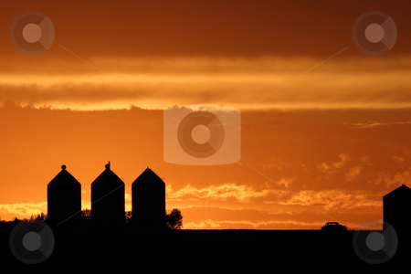 Colorful sunset behind granaries stock photo, Colorful sunset behind granaries by Mark Duffy
