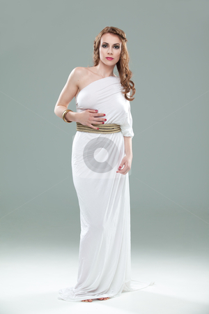 Portrait of young woman in greek inspired white dress, smiling stock photo, a studio portrait of a beautiful young woman, wearing a long, white, ancient greek inspired dress, smiling. by dan comaniciu